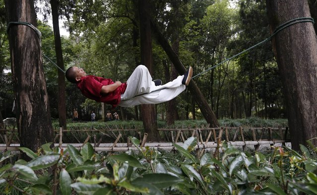 Liang Yanguo, 51, naps as he lies on a rope tied between two trees, as a form of martial arts practice, at a park in Huangyan district of Taizhou, Zhejiang province September 18, 2014. Liang was training in martial arts and free combat until he was diagnosed with late stage throat cancer three years ago. After having surgery, he invented the rope method as a more relaxed way to continue practicing martial arts and keep his body healthy, local media reported. (Photo by William Hong/Reuters)