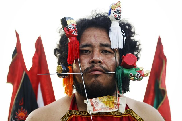 A devotee of Ban Tha Rua Chinese shrine with his cheeks pierced gets ready for a street procession celebrating the annual vegetarian festival in Phuket September 28, 2014. (Photo by Damir Sagolj/Reuters)
