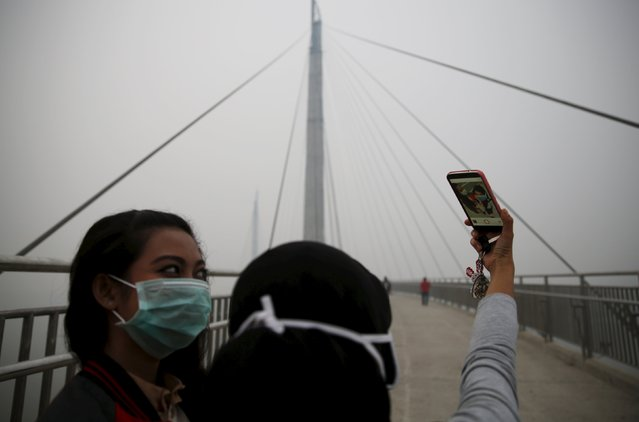 "Girls take a selfie at the haze shrouded Batanghari River bridge in Jambi, Indonesia Sumatra island, September 14, 2015. Indonesian islands are blanketed in the so-called ""haze"", caused by slash-and-burn clearances on the islands of Sumatra and Borneo, which makes thousands sick, delays flights and pushes air quality to unhealthy levels in neighboring Singapore and Malaysia. (Photo by Reuters/Beawiharta)"