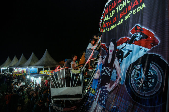 """A picture made available on 16 August 2016 shows spectators queuing to watch the female dare devil motorbike rider, Karmila Purba inside a barrel locally known as """"Tong Setan"""" or Davil's Barrel, at a traditional night carnival in Deliserdang, North Sumatra, Indonesia, 13 August 2016. (Photo by Dedi Sinuhaji/EPA)"""