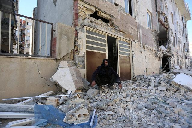 A man sits outside a damaged belonging following an earthquake in Sarpol-e Zahab county in Kermanshah, Iran, Monday, November 13, 2017. (Photo by Reuters/Tasnim News Agency)