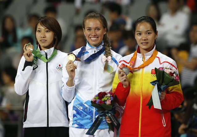 Kazakhstan's gold medallist Olga Safronova (C), China's silver medallist Wei Yongli (R) and Japan's bronze medallist Chisato Fukushima pose during the medal ceremony for the women's 200m final at the Incheon Asiad Main Stadium during the 17th Asian Games October 1, 2014. (Photo by Jason Reed/Reuters)