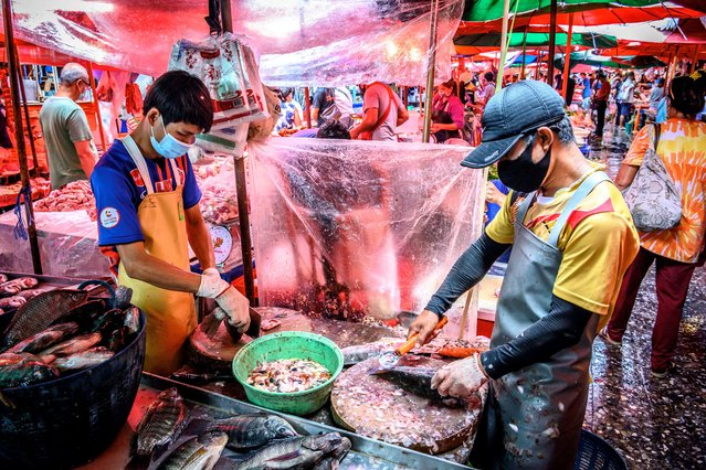 Vendors clean fish at Khlong Toei Market, the biggest fresh market in Bangkok, on June 18, 2020. A huge wholesale market has become the centre of focus for a new cluster of coronavirus cases in Beijing, where nervous local officials have begun mass testing, closing schools and neighbourhoods, and turned sharp scrutiny towards the food supply chain. (Photo by Mladen Antonov/AFP Photo)