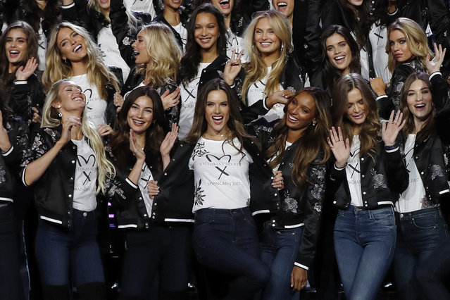 Model of the Victoria's Secret Fashion Show Alessandra Ambrosio from Brazil, front row center, displays a Victoria's Secret Shanghai t-shirt as she poses next to Adriana Lima of Brazil, front row center left, and Jasmine Tookes of the United States, front row center right, together with other models during a group photo on stage at the Mercedes-Benz Arena in Shanghai, China, Saturday, November 18, 2017. Victoria's Secret Fashion Show is taking place in Shanghai on Nov. 20 featuring lingerie embellished with Swarovski crystals, the iconic angel wings, heels designed by Brian Atwood and a $2 million Champagne Nights Fantasy Bra designed exclusively for Victoria's Secret by Mouawad and modeled by Angel Lais Ribeiro. (Photo by Andy Wong/AP Photo)