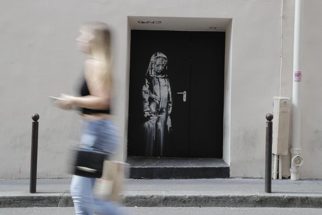 In this file photo taken on June 25, 2018 a woman walks past a recent artwork by street artist Banksy in Paris on a side street to the Bataclan concert hall where a terrorist attack killed 90 people on Novembre 13, 2015. The stolen Banksy work has been found in Italy, AFP reports on June 10, 2020. (Photo by Thomas Samson/AFP Photo)