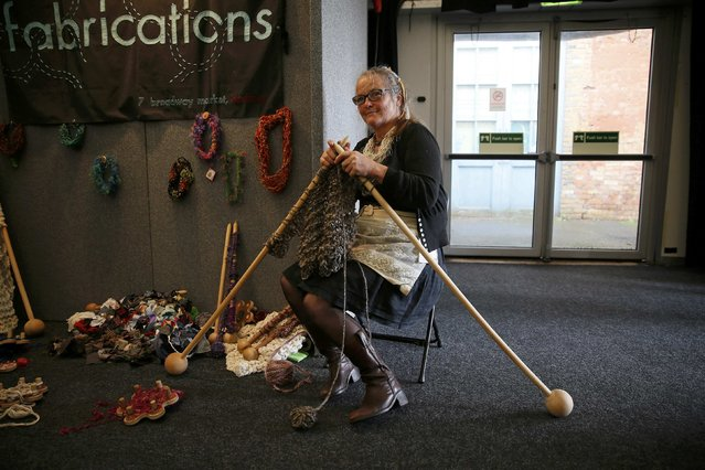 A woman knits with large knitting needles during the Knitting and Stitching show at Alexandra Palace in London, October 8, 2014. The show which includes over 600 exhibitors and 300 workshops is the largest textile and craft event in Britain. (Photo by Stefan Wermuth/Reuters)