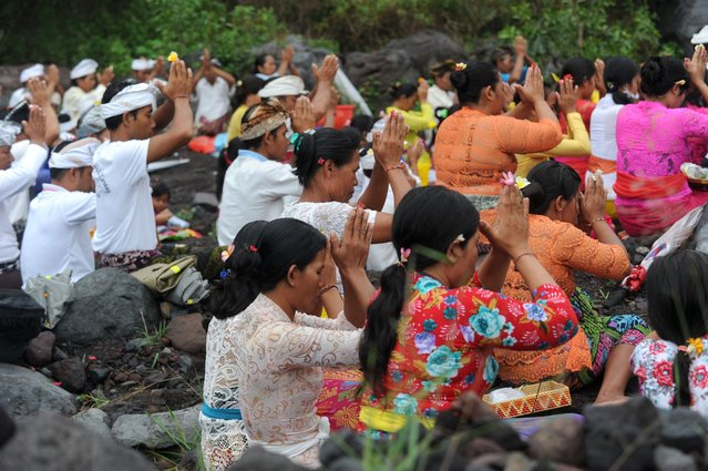 Balinese Hindus take part in a ceremony, where they pray near Mount Agung in hope of preventing a volcanic eruption, in Muntig village of the Kubu sub-district in Karangasem Regency on Indonesia's resort island of Bali on November 26, 2017. (Photo by Sonny Tumbelaka/AFP Photo)