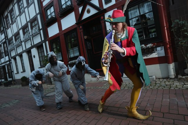 The Pied Piper of Hamelin, actually city tourism employee Michael Boyer, leads local children dressed as rats through a quiet street on November 19, 2012 in Hameln, Germany. The Pied Piper (in German: Der Rattenfaenger), is one of the many stories featured in the collection of fairy tales collected by the Grimm brothers, and the 200th anniversary of the first publication of the stories will take place this coming December 20th. Boyer, a U.S. citizen who has lived in Hameln for 15 years, and city children regularly perform a reenactment of the Pied Piper tale throughout the summer months. The Grimm brothers collected their stories from oral traditions in the region between Frankfurt and Bremen in the early 19th century, and the works include such global classics as Sleeping Beauty, Little Red Riding Hood, Rapunzel, Cinderella and Hansel and Gretel.  (Photo by Sean Gallup)