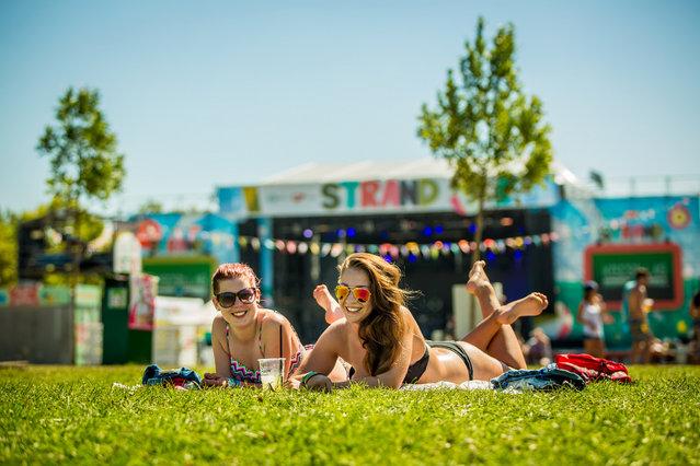Festival goers sunbathe during the double festivals Strand (Beach) and B.my.Lake at Lake Balaton in Zamardi, 112 kms southwest of Budapest, Hungary, 26 August 2016. (Photo by Mudra László/Rockstar Photographers)