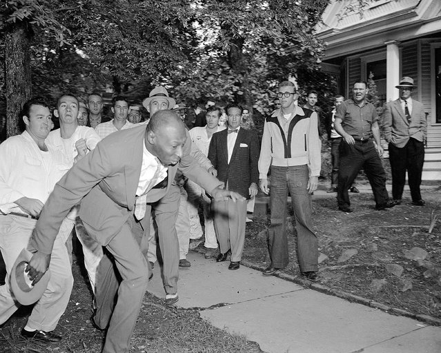 A reporter from the Tri-State Defender, Alex Wilson, is shoved by an angry mob of white people near Central High School in Little Rock, Ark., September 23, 1957.  The fight started when nine black students gained entrance to the school as the Army enforced integration. (Photo by AP Photo)