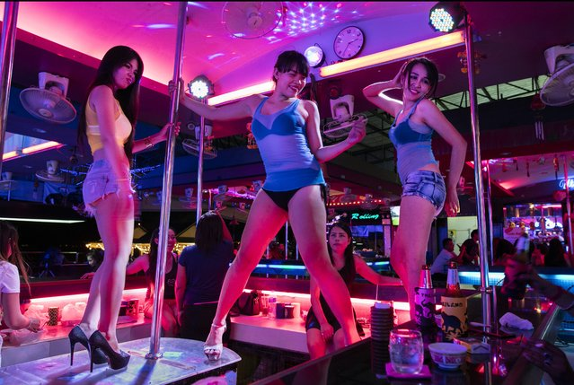 Bar girls entertain Indian men at a bar along the Walking Street where bars and s*x scenes are a commonplace July 31, 2016 in Pattaya, Thailand. (Photo by Paula Bronstein/Getty Images)