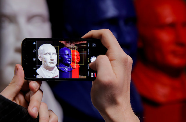 """A man takes a picture of the busts depicting Russian president Vladimir Putin in the colors of the Russian national flag at the """"SUPERPUTIN"""" exhibition at UMAM museum in Moscow, Russia on December 6, 2017. (Photo by Maxim Shemetov/Reuters)"""