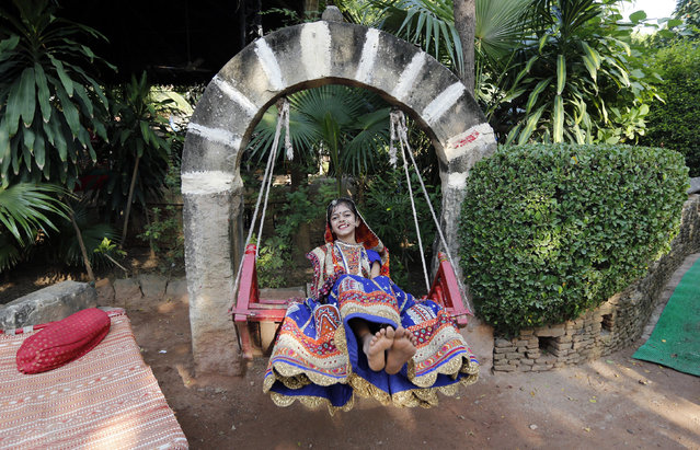 "A girl dressed in traditional attire plays on a swing after taking part in rehearsals for the ""garba"" dance ahead of the Navratri festival in Ahmedabad September 21, 2014. (Photo by Amit Dave/Reuters)"