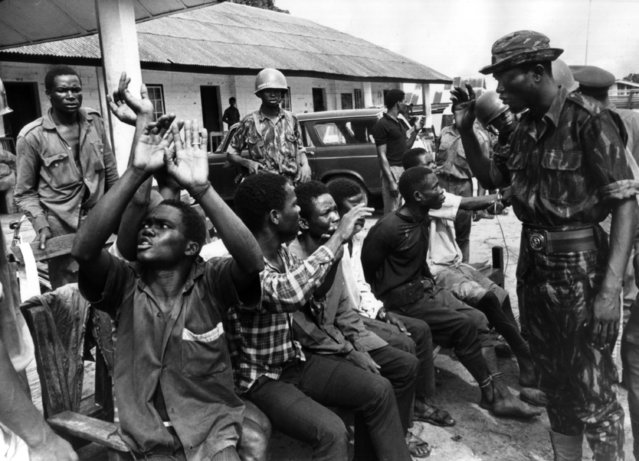 An Ibo soldier captured by Nigerian federal troops near Owerri in Biafra throws his hands up in anguish as hIS captors tell him he will be sentenced to death as a traitor, September 30, 1968. (Photo by Dennis Lee Royle/AP Photo)