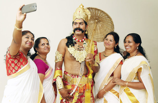 "Indian women wearing traditional attire take a ""selfie"" with an Indian man dressed as King 'Mahabali' during the Hindu harvesting festival Onam celebrations in Bangalore, India, 28 August 2015. Local people put flower mats in front of their houses, to welcome the King Mahabali, a past ruler of Kerala southern India, during the ten-day festival. (Photo by Jagadeesh N. V./EPA)"