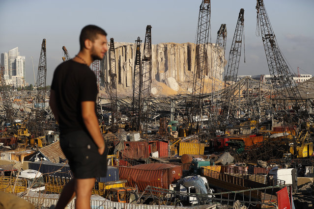 A man looks at the scene of Tuesday's explosion that hit the seaport of Beirut, Lebanon, Friday, August 7, 2020. Rescue teams were still searching the rubble of Beirut's port for bodies on Friday, nearly three days after a massive explosion sent a wave of destruction through Lebanon's capital. (Photo by Hussein Malla/AP Photo)