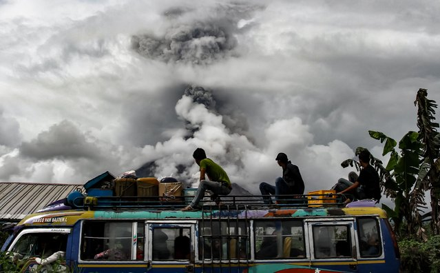 Indonesian bus passengers watch as Mount Sinabung spews thick smoke in Karo, North Sumatra on January 2, 2018. Mount Sinabung roared back to life in 2010 for the first time in 400 years, after another period of inactivity it erupted once more in 2013, and has remained highly active since. (Photo by Ivan Damanik/AFP Photo)