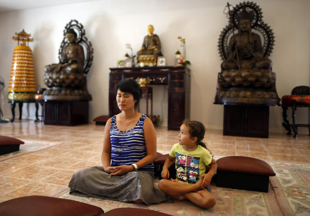 Sarah Kim, who emigrated from South Korea, meditates with Sabina Mayorga, 4, whose parents are from Mexico, at Lu Mountain Buddhist Temple in Rosemead, California August 15, 2014. (Photo by Lucy Nicholson/Reuters)