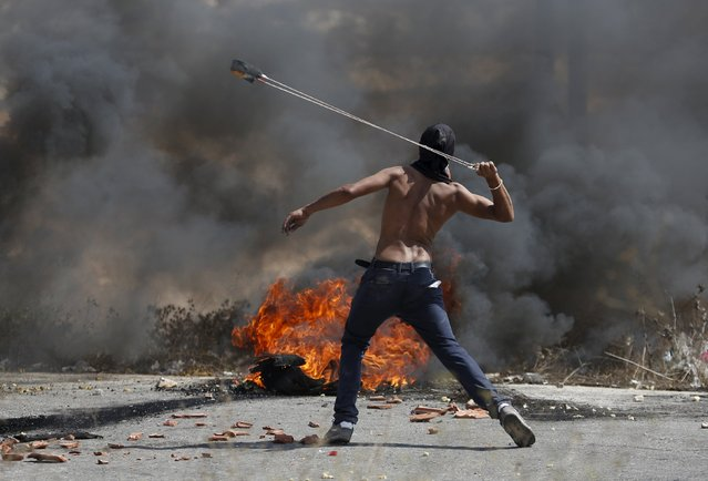 A Palestinian protester uses a sling to hurl stones towards Israeli troops during clashes near the Jewish settlement of Bet El, near the occupied West Bank city of Ramallah October 5, 2015. Violence intensified in Jerusalem and the West Bank on Sunday after Israelis were targeted in two stabbing attacks and a Palestinian was killed in a clash with Israeli troops, officials said. (Photo by Mohamad Torokman/Reuters)
