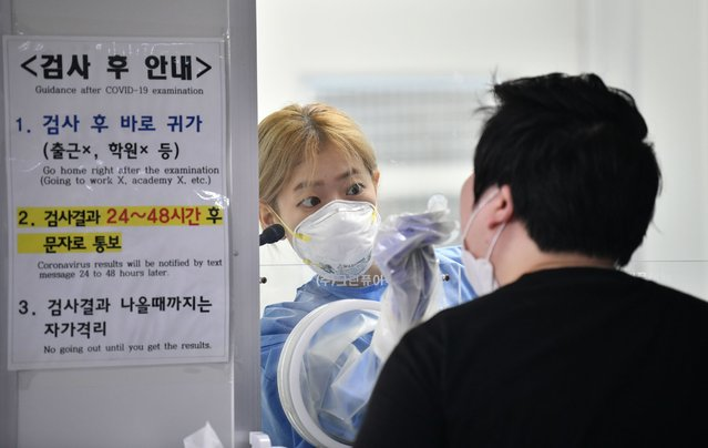 A medical staff in a booth takes test samples for the COVID-19 coronavirus from a visitor at a coronavirus testing station in Seoul on August 18, 2020. South Korea on August 18 ordered nightclubs, museums and buffet restaurants closed and banned large-scale gatherings in and around the capital as a burst of new coronavirus cases sparked fears of a major second wave. (Photo by Jung Yeon-je/AFP Photo)