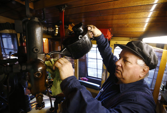 Puffing Billy steam engine driver Steve Holmes, 61, tops up the oil in a displacement lubricator in the cab of locomotive 12A as he prepares the engine for service at Belgrave near Melbourne, October 20, 2014. (Photo by Jason Reed/Reuters)