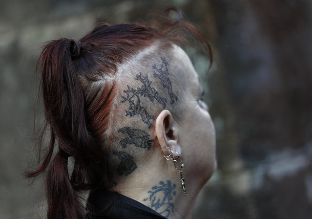A woman with tattoos of the Abbots Bromley Horn Dance watches dancers in Abbots Bromley, Britain, September 12, 2016. (Photo by Darren Staples/Reuters)