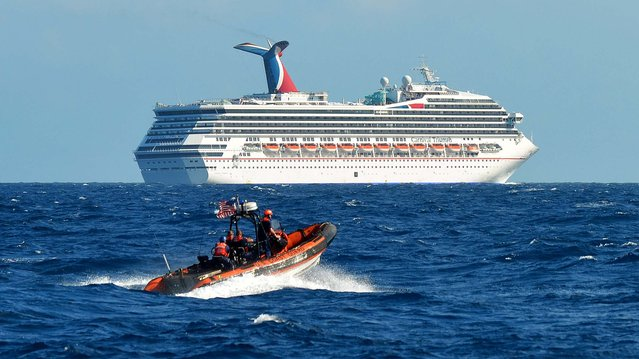 A small boat belonging to the Coast Guard Cutter Vigorous patrols near the cruise ship Carnival Triumph in the Gulf of Mexico on February 11, 2013. The Carnival Triumph has been floating aimlessly about 150 miles off the Yucatan Peninsula since a fire erupted in the aft engine room early Sunday, knocking out the ship's propulsion system. No one was injured and the fire was extinguished. (Photo by Lt. Cmdr. Paul McConnell/U.S. Coast Guard)