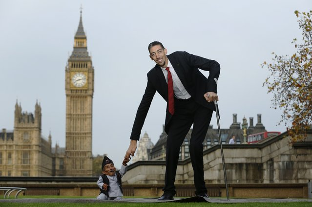 The world's shortest man Chandra Bahadur Dangi greets the tallest living man Sultan Kosen to mark the Guinness World Records Day in London November 13, 2014.  Kosen measuring 251cm, towers over Dangi who is only 54.6cm tall. The Guinness World Records celebrates its 60th edition of the annual records book. (Photo by Luke MacGregor/Reuters)
