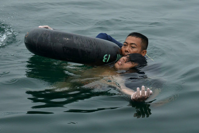 In this handout photograph released by the Indonesian Navy on October 13, 2015, an Indonesian Navy diver rescues helicopter crash survivor Fransiskus Subihardayan after he was found by the search and rescue team in Lake Toba, western Sumatra island on October 13, 2015. (Photo by AFP Photo/Indonesian Navy)