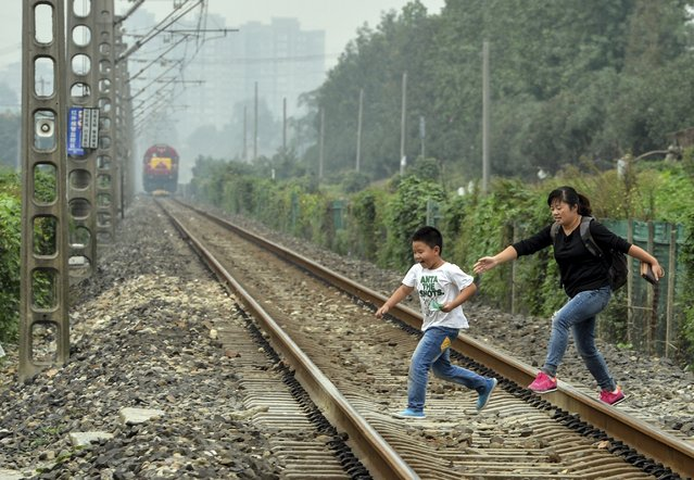 A boy and a woman run across a railway track as a train approaches in Chengdu, Sichuan province, China, October 8, 2015. Many residents disregard sign prohibiting this kind of illegal crossing and choose to do so to save time, local media reported. (Photo by Hao Fei/Reuters/Western China Metropolis Daily)