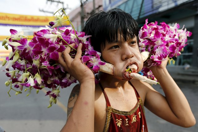 A devotee of the Chinese Samkong Shrine walks with flowers pierced through his cheeks during a procession celebrating the annual vegetarian festival in Phuket, Thailand, October 16, 2015. (Photo by Jorge Silva/Reuters)