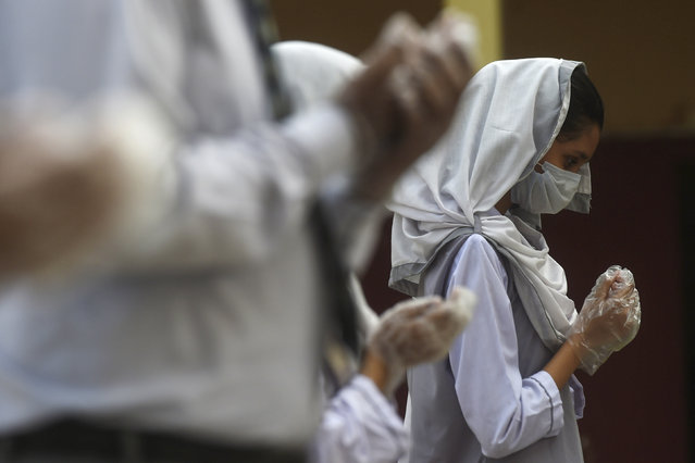 A student wearing a facemask and gloves takes part in an assembly at a school in Karachi on September 15, 2020 after the educational institutes were reopened nearly six months after the spread of the Covid-19 coronavirus. (Photo by Asif Hassan/AFP Photo)