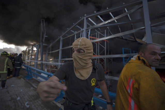 Firefighters work to extinguish a fire at warehouses at the seaport in Beirut, Lebanon, Thursday, September 10. 2020. (Photo by Hussein Malla/AP Photo)