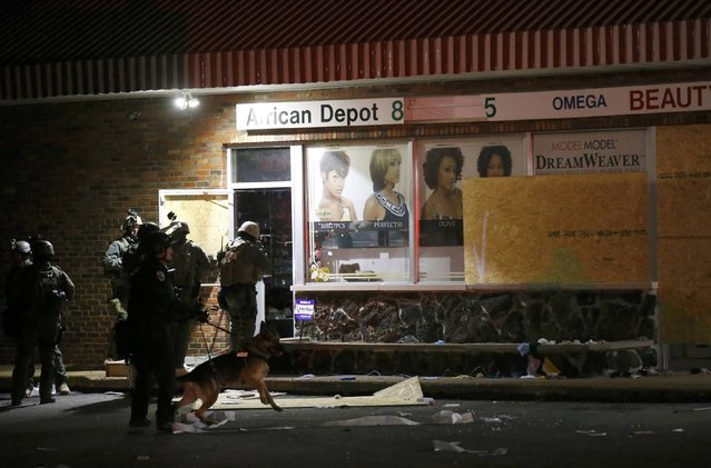 Police search a building following rioting after a grand jury returned no indictment in the shooting of Michael Brown in Ferguson, Missouri November 24, 2014. (Photo by Jim Young/Reuters)