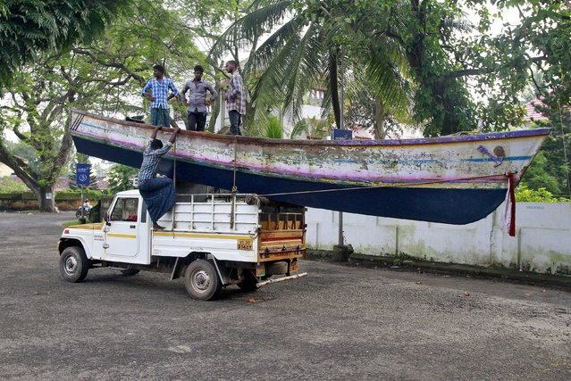A fisherman climbs down from a jeep as others stand in a boat tied atop the vehicle after it was transported from a beach in Kochi, India, October 20, 2015. (Photo by Sivaram V/Reuters)