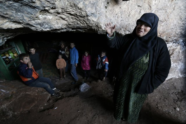 A displaced woman, standing with children, gestures as she talks inside an underground cave in Jabal al-Zawiya in the southern countryside of Idlib November 26, 2014. (Photo by Khalil Ashawi/Reuters)