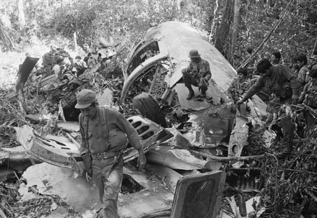Sandinista soldiers walk amid the debris after shooting down a supply plane of the U.S. backed rebels in Loma El Arenal, Nicaragua, a Defense Ministry source said  Sunday, January 24, 1988. Rebel spokeswomen said the craft was a DC -6 and 11 crew members were killed. (Photo by Mario Tapia/AP Photo)