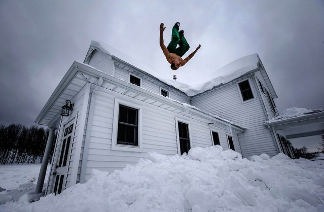 Phil Mohun does a back flip off of his family home after clearing snow from the roof following a massive snowstorm in Cowlesville, New York, November 22, 2014. Warm temperatures and rain were forecast for the weekend in the city of Buffalo and western New York, bringing the threat of widespread flooding to the region bound for days by deep snow. (Photo by Mark Blinch/Reuters)