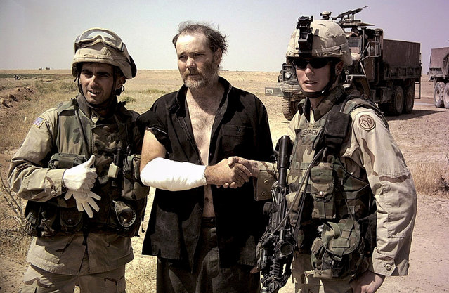 Former hostage Thomas Hamill, center, is seen with two U.S. Army soldiers, shortly after his escape south of Tikrit, in this picture released on Monday, May 3, 2004. Hamill, who escaped from captivity during the weekend, left Iraq and stopped by a military hospital in Germany for a check-up, a U.S. military official said. (Photo by AP Photo/U.S Army/The Atlantic)
