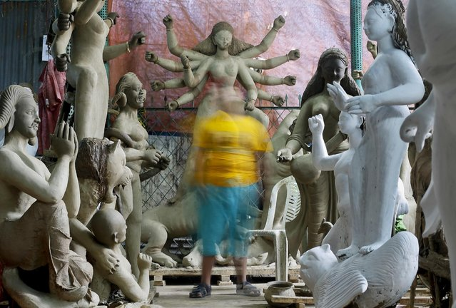 A Bangladeshi child walks past idols being prepared for the upcoming Durga Puja Hindu festival in Dhaka, Bangladesh, Saturday, September 24, 2016. The five-day festival commemorates the slaying of a demon king by goddess Durga, marking the triumph of good over evil. (Photo by A.M.Ahad/AP Photo)