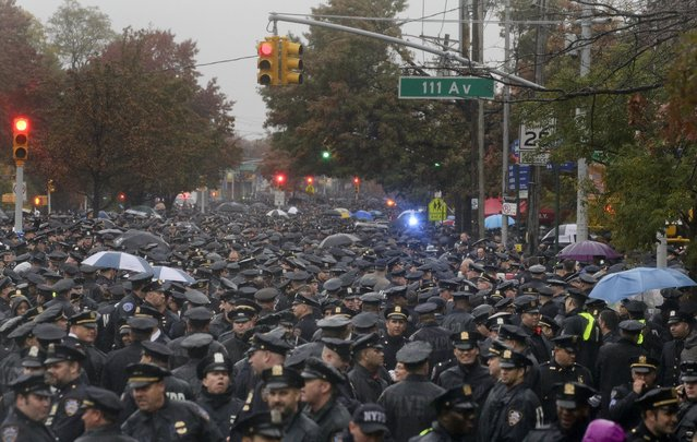 Hundreds of New York police officers gather in the street outside a church for the funeral of Officer Randolph Holder, Wednesday, October 28, 2015, in New York. Holder was killed on Oct. 20 while responding to a report of shots fired and a bicycle stolen at gunpoint in Manhattan's East Harlem neighborhood. (Photo by Julie Jacobson)/AP Photo