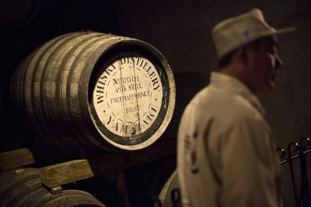 Senior General Manager of Suntory Holdings' Yamazaki Distillery Takahisa Fujii stands in front of the distillery's oldest cask, filled in 1924, in its storage in Shimamoto town, Osaka prefecture, near Kyoto, December 1, 2014. (Photo by Thomas Peter/Reuters)
