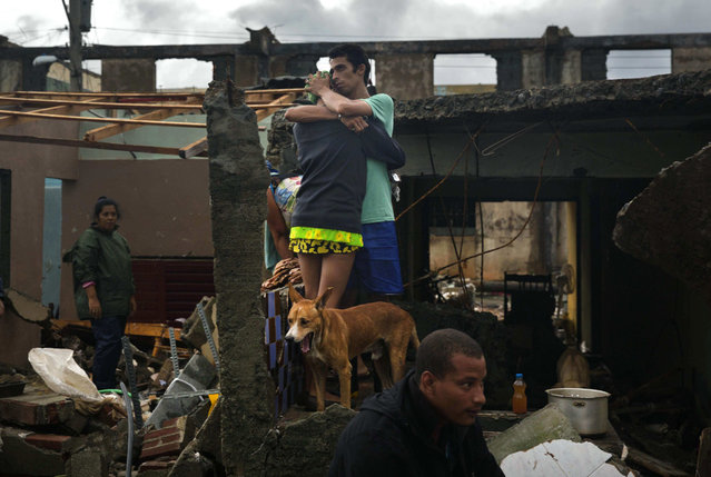 A couple embrace standing among the debris of their home destroyed by Hurricane Matthew in Baracoa, Cuba, Wednesday, October 5, 2016. (Photo by Ramon Espinosa/AP Photo)