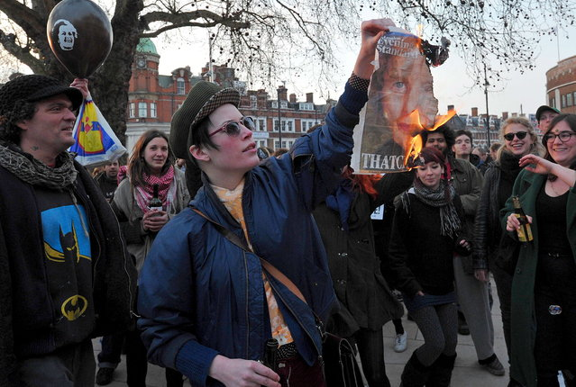 "A woman burns a newspaper page showing an image of former British Prime Minister Margaret Thatcher during a ""party"" to celebrate the death of Margaret Thatcher in London, on April 8, 2013.  Margaret Thatcher, the ""Iron Lady"" who shaped a generation of British politics, died following a stroke on Monday at the age of 87, her spokesman said. (Photo by Carl Court/AFP Photo)"