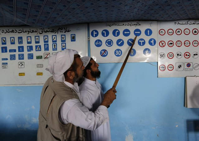 An instructor explains traffic signs to a man during a lesson at a driving school in Kabul August 24, 2014. (Photo by Mohammad Ismail/Reuters)