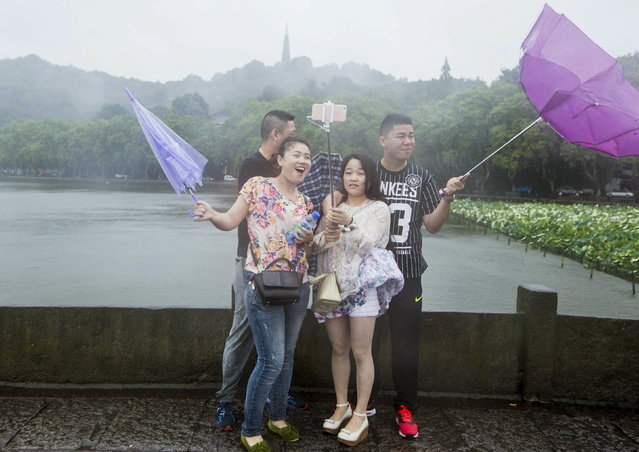 Tourists hold umbrellas as they take a picture with a selfie stick next to the West Lake against strong wind under the influence of Typhoon Chan-hom, in Hangzhou, Zhejiang province, China, July 11, 2015. (Photo by Reuters/Stringer)