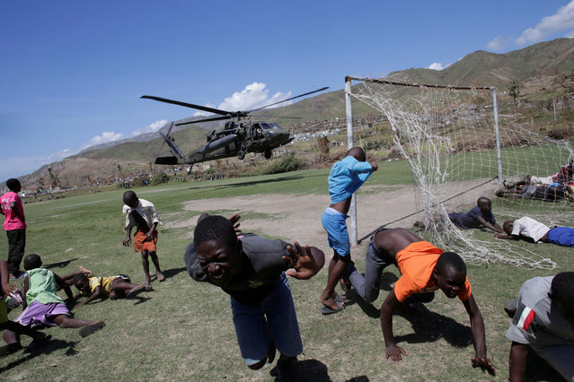 Haitian run away as a helicopter of US forces takes off after leaving food suplies for residents after Hurricane Matthew in Les Anglais, Haiti, October 12, 2016. (Photo by Andres Martinez Casares/Reuters)