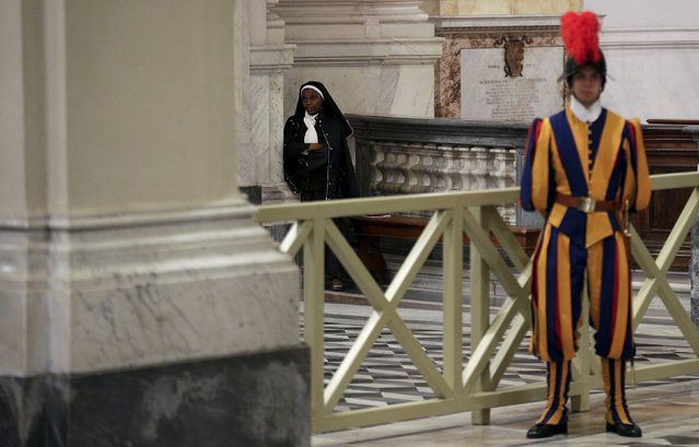 A nun and a Swiss guard attend a mass led by Pope Francis at Archbasilica of St. John Lateran in Rome, November 9, 2015. (Photo by Max Rossi/Reuters)