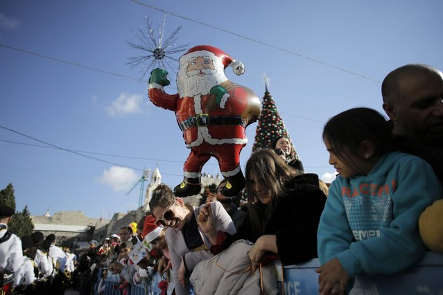 People watch Christmas celebrations outside the Church of the Nativity, the site revered by Christians as Jesus' birthplace, in the West Bank town of Bethlehem December 24, 2014. (Photo by Ammar Awad/Reuters)