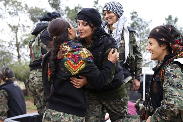 A Kurdish People's Protection Units (YPG) fighter hugs a fellow fighter in a YPG military base east of Qamishli, Syria, before heading to Jazaa and Tal Kojar frontlines December 19, 2014. (Photo by Massoud Mohammed/Reuters)